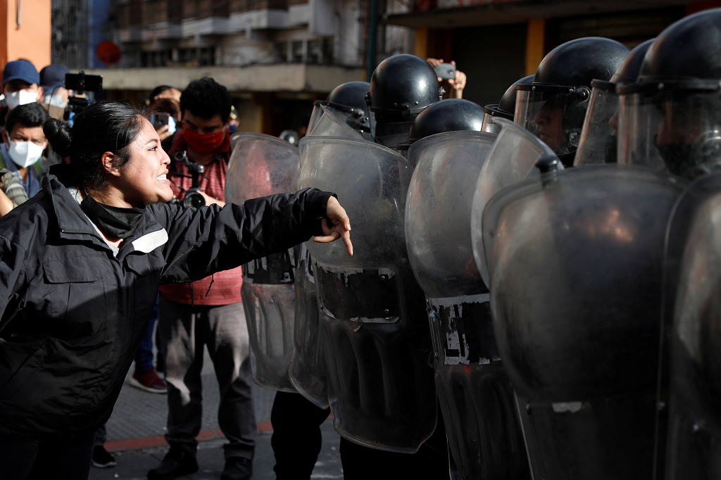 A demonstrator shouts at riot police during protests in Guatemala City. [Luis Echeverria/Reuters]
